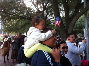 A young girl waves a flag from atop her father's shoulders.