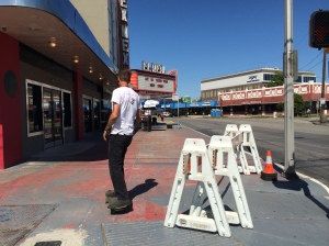 Shortly before the Sunday Streets event begins, a skateboarder zips past the El Rey restaurant, a former movie theater.
