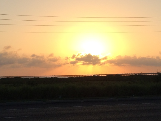 The sun begins to set behind the Causeway leading to South Padre Island, Texas.