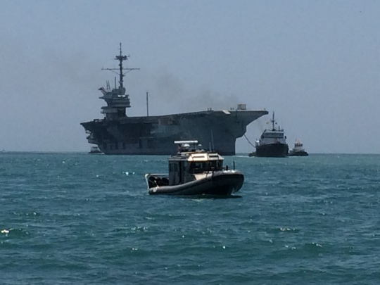 Tug boats and other small craft escort the USS Ranger.